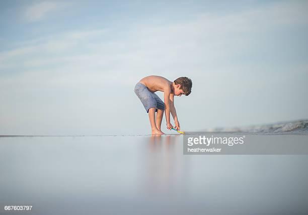 Boy digging on beach, Florida, America, USA