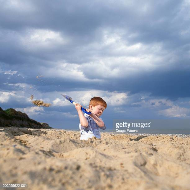 Boy (4-6) digging sand pit on beach, smiling, ground view