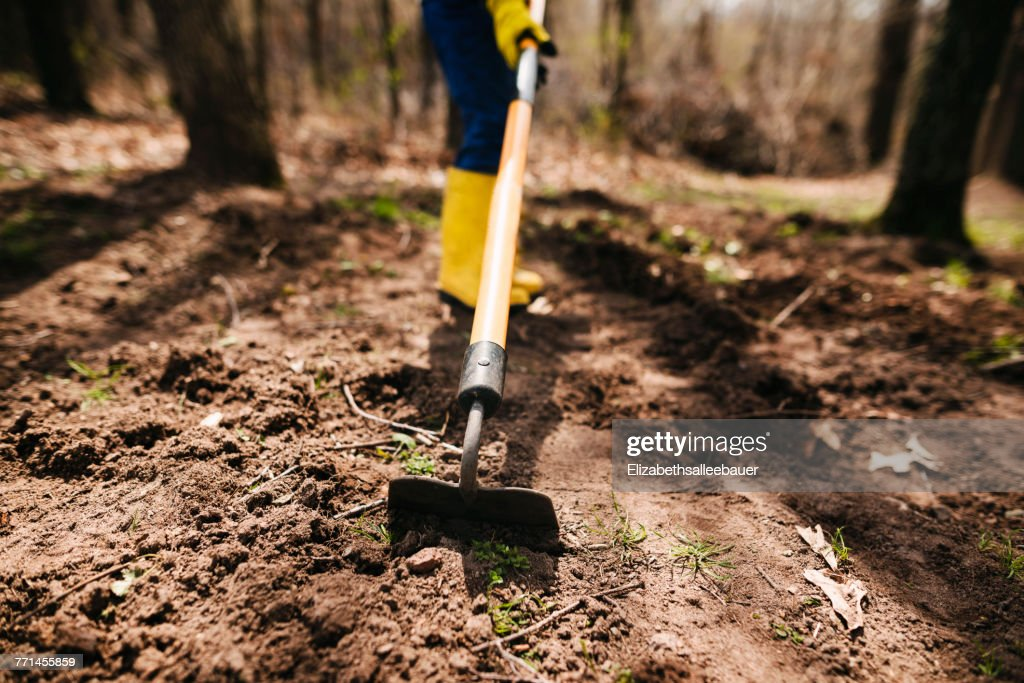 boy digging the soil with a hoe - Garden Hoe