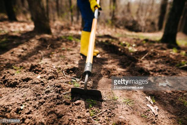 boy digging the soil with a hoe - 耕す ストックフォトと画像