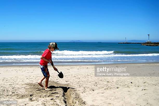 Boy digging trench at beach