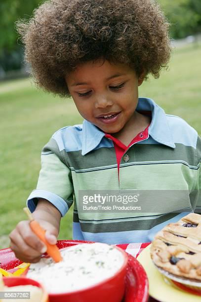 Boy Dipping Carrot Stick into Dip