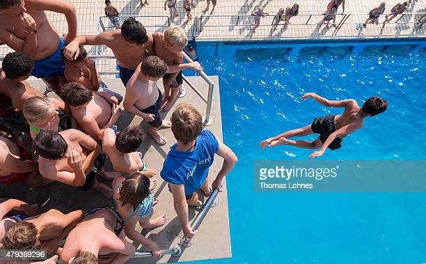 A boy dives from the 3 meter platform while children and teens wait for the jump into the swimming pool 'Muehltalbad' on July 03 2015 in Darmstadt...