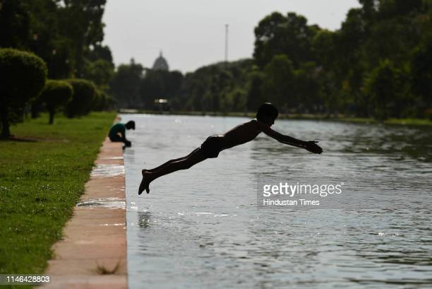A boy dives in a pond to beat the heat on a summer day at Rajpath on May 27 2019 in New Delhi India
