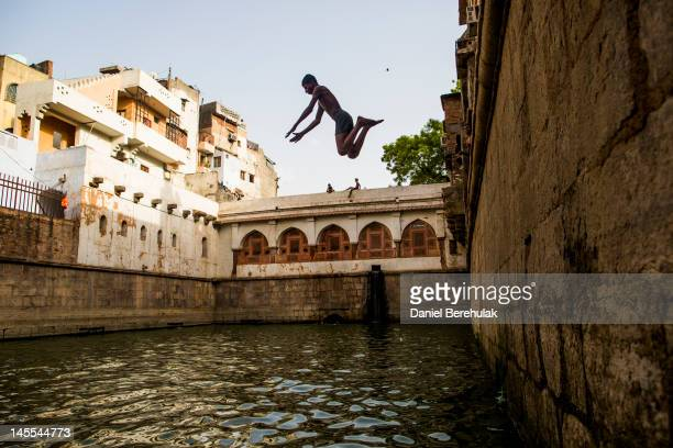A boy dives in to the stepwell at the Nizamuddin Dargah on June 1 2012 in New Delhi India A Heat wave is continuing across the Northern India capital...