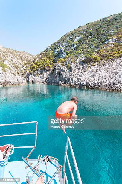 Boy diving in the sea from sail boat.  Greece