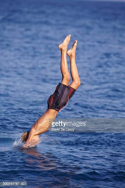 boy diving in to sea - jungen in badehose 12 jahre stock-fotos und bilder