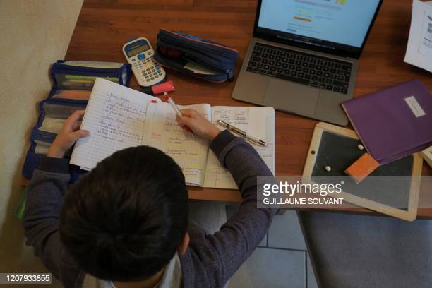 A boy does his homework at home on March 21 2020 in the central France city of MontlouissurLoire on the fifth day of a strict nationwide confinement...
