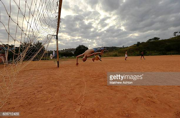 Boy doing acrobatics with a footbball next to a rustic goal net on a dust football pitch situated in between Rua Coronel Manuel Assuncao, Belo...