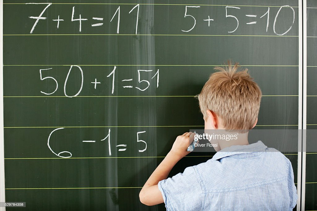 Boy doing arithmetic on blackboard : Stockfoto