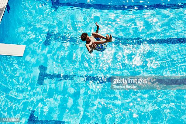 Boy doing backflip off diving board into pool