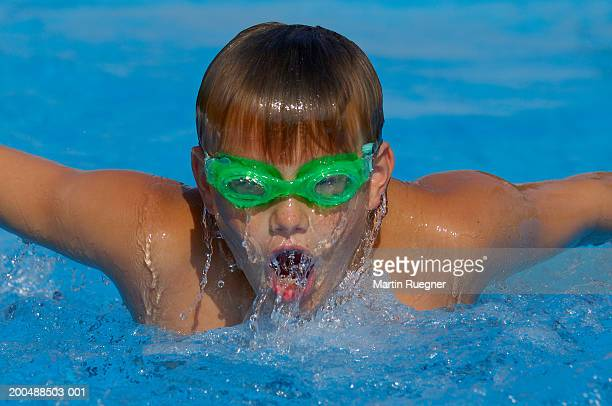 Boy (12-14) doing butterfly stroke, close-up