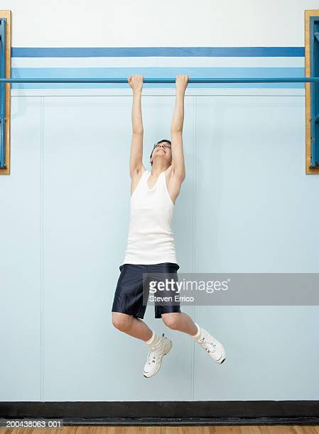 Boy (11-13) doing chin-ups in school gymnasium