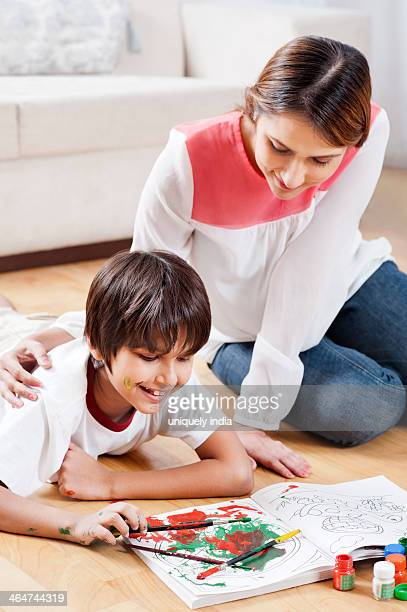 Boy doing coloring with his mother sitting beside him