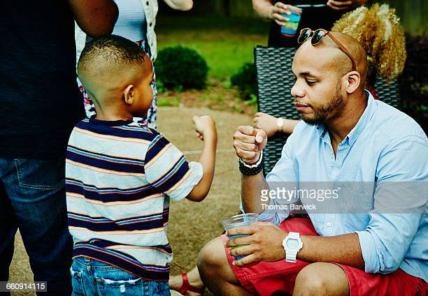 Boy doing fist bumps with uncle during party