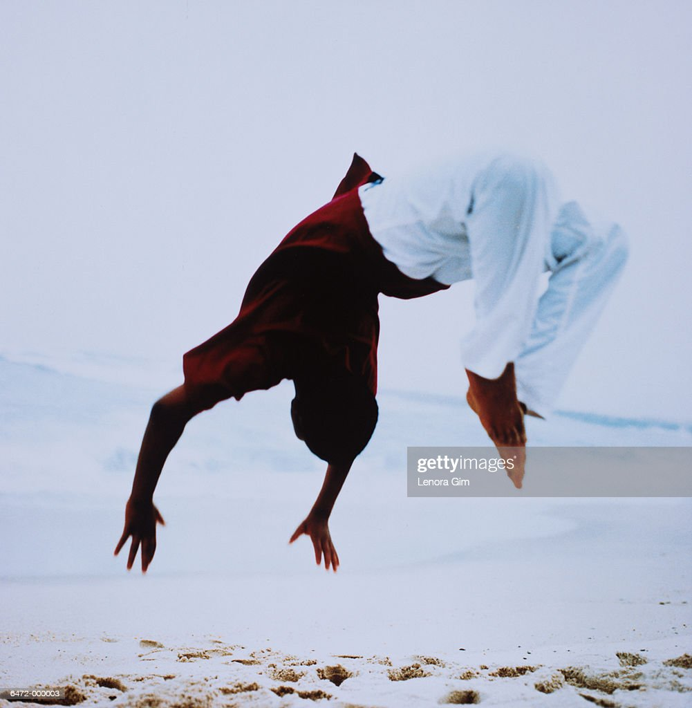 e22eed98a6e1c0 Boy Doing Flip on Beach   Stock Photo