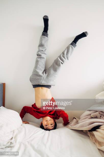 boy doing headstand on bed - peter lourenco stock pictures, royalty-free photos & images