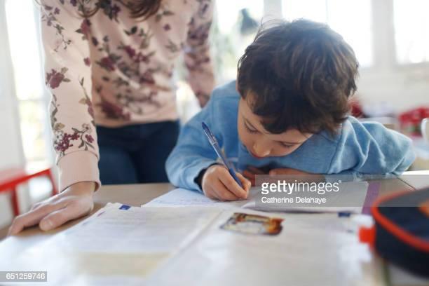 a boy doing his homeworks - hausaufgabe stock-fotos und bilder