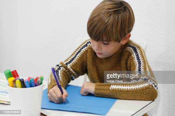 boy doing homework at home - primary age child stock pictures, royalty-free photos & images