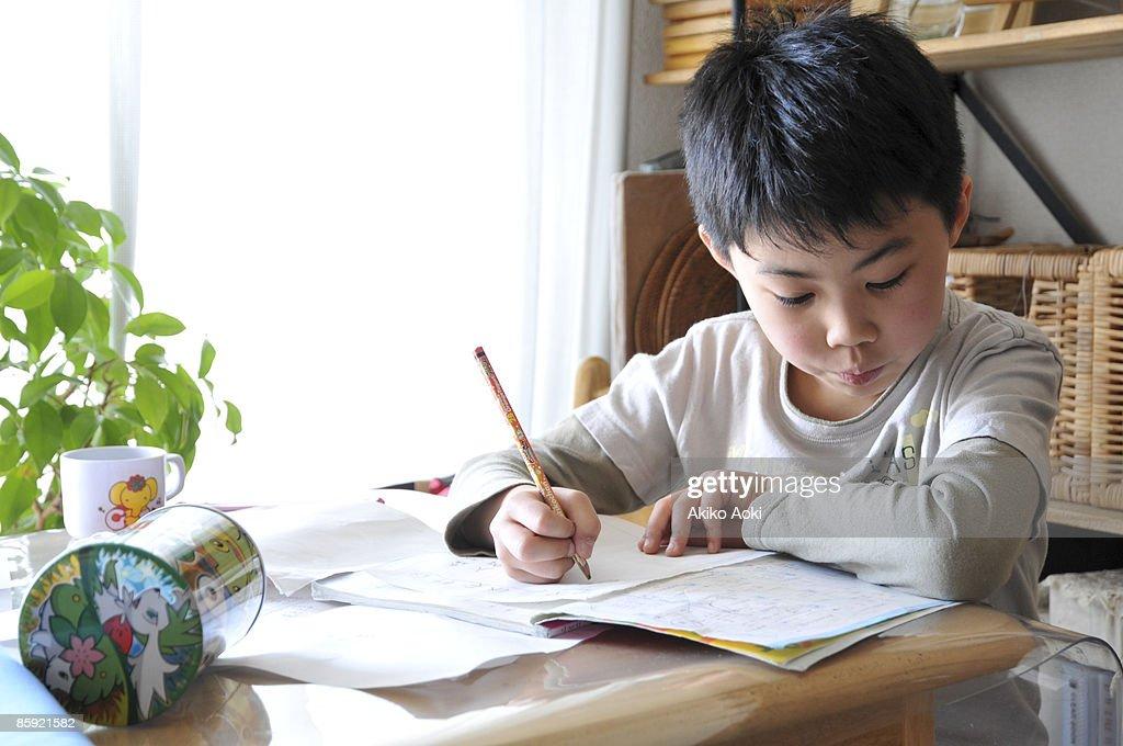 A boy doing homework : Stock Photo