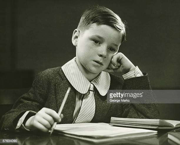 boy (8-9) doing homework, (b&w), portrait - only boys stock pictures, royalty-free photos & images
