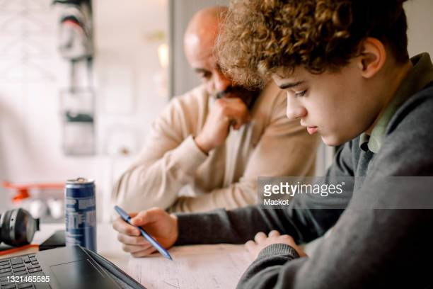 boy doing homework while sitting by father at home - homework stock pictures, royalty-free photos & images