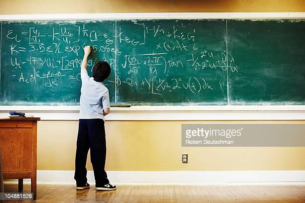 boy doing math at chalkboard - un solo niño fotografías e imágenes de stock