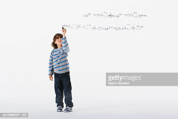 Boy (6-7) doing mathematical equation, on white background