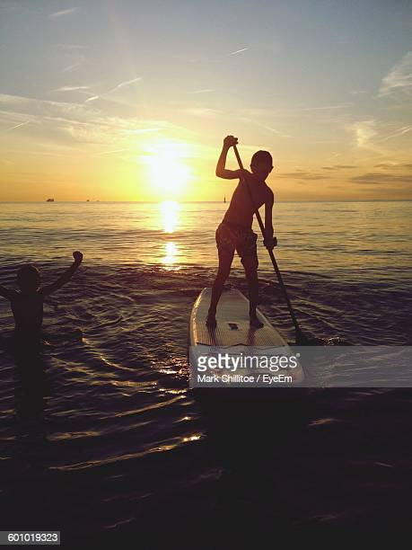 Boy Doing Paddleboarding On Sea Against Sky During Sunset
