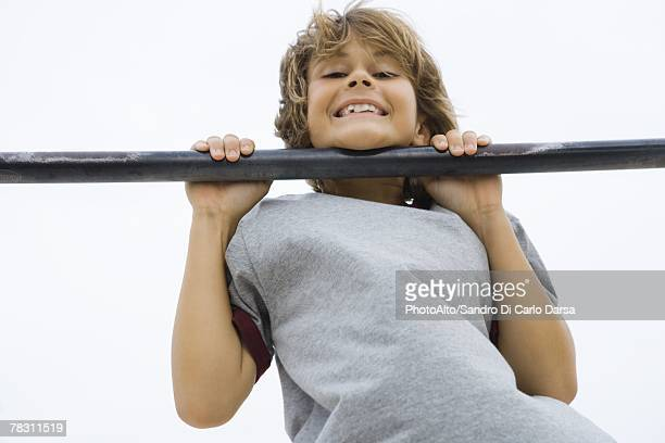 Boy doing pull-up, chin resting on bar, smiling at camera