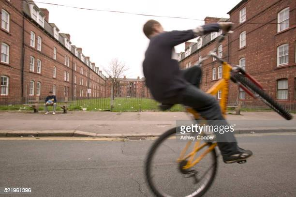Boy Doing Wheelie by Tenement Block