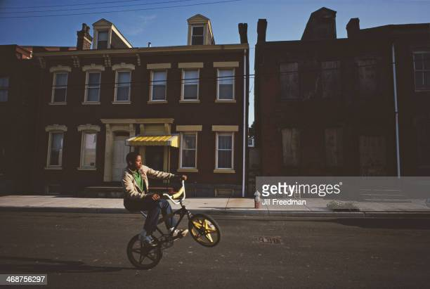 A boy doing wheelies in a street in Pittsburgh Pennsylvania September 1983