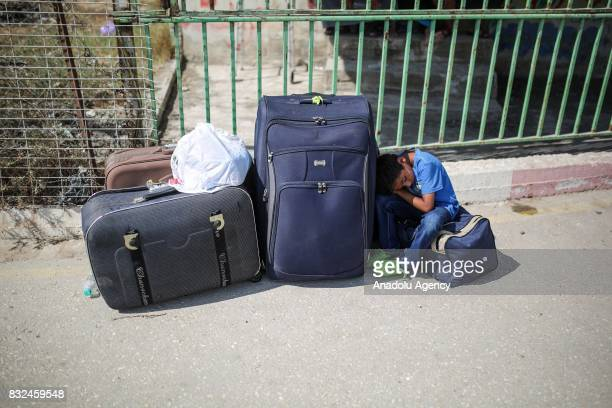 A boy dozes off as he waits to cross the Rafah Border with his luggages in Rafah Gaza on August 16 2017 Egypt decided to open Rafah Border Gate for...