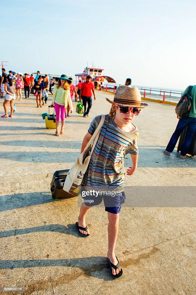 Boy Dragging Suitcase Along Boardwalk High-Res Stock Photo