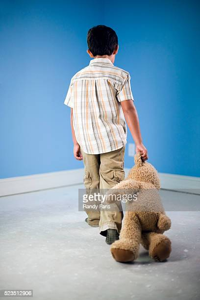 boy dragging teddy bear into time-out corner - dragging stock pictures, royalty-free photos & images