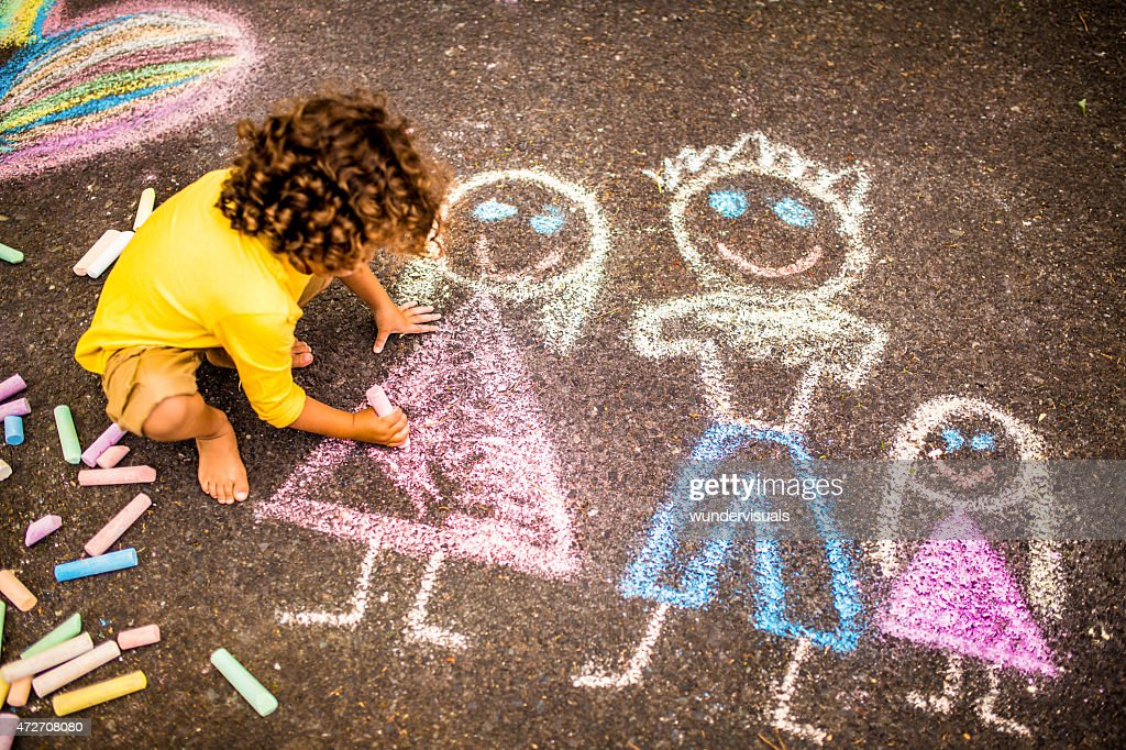 Boy drawing a colourful chalk picture of his family : Stockfoto