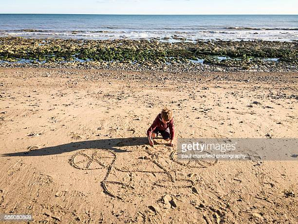 Boy drawing bicycle on a sandy beach