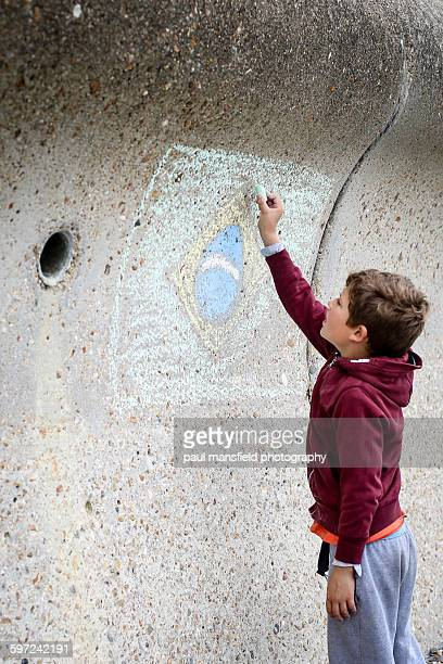 Boy drawing Brazil flag on wall