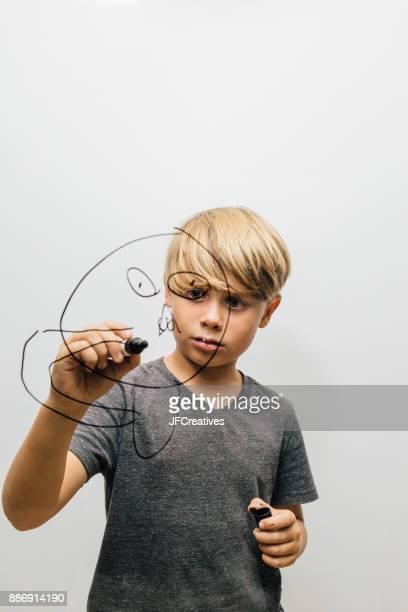 Boy drawing face with marker pen onto glass wall