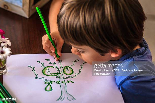 Boy drawing green tree picture