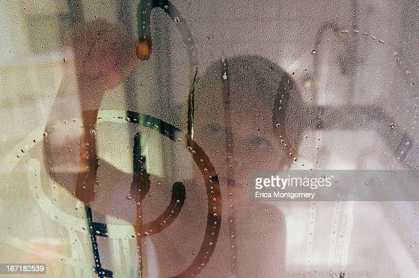 boy (6-7) drawing happy face on shower glass