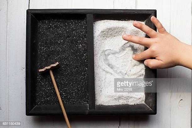 Boy drawing heart shape in sand in mini Japanese zen garden