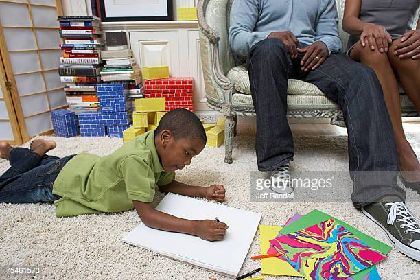 boy (6-7) drawing in book, parents watching - colouring book stock pictures, royalty-free photos & images