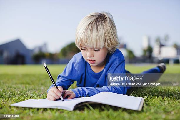 Boy drawing in grass