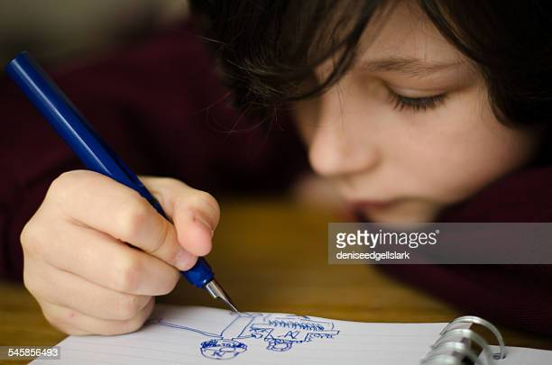 Boy drawing in note pad