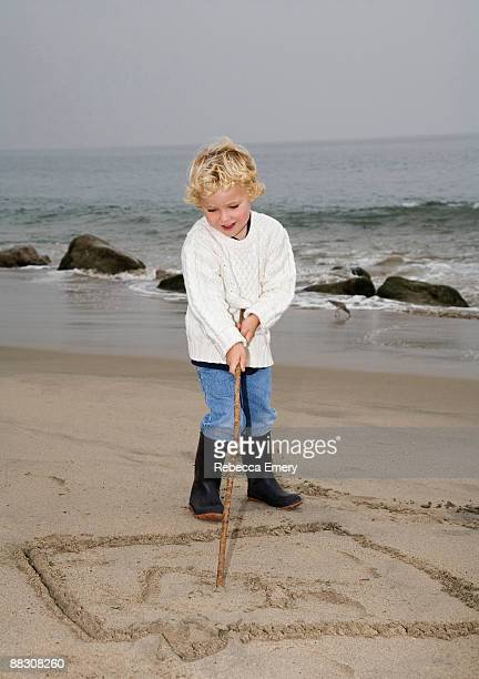 boy drawing in sand on beach - emery stock photos and pictures