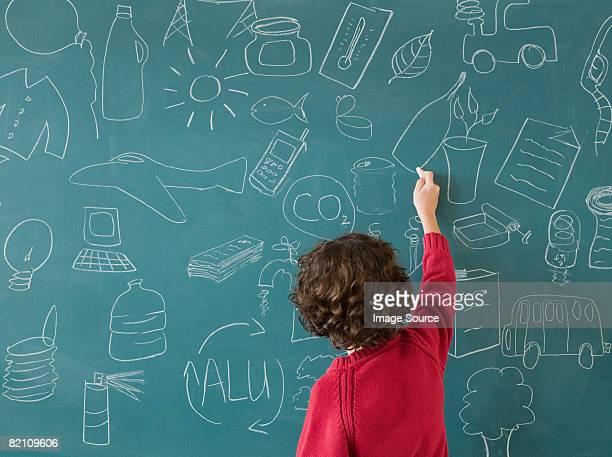 Boy drawing on a blackboard