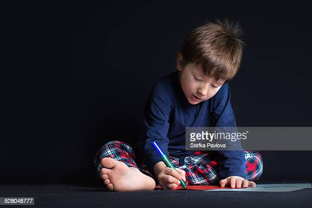 Boy drawing on a sheet of paper on the floor