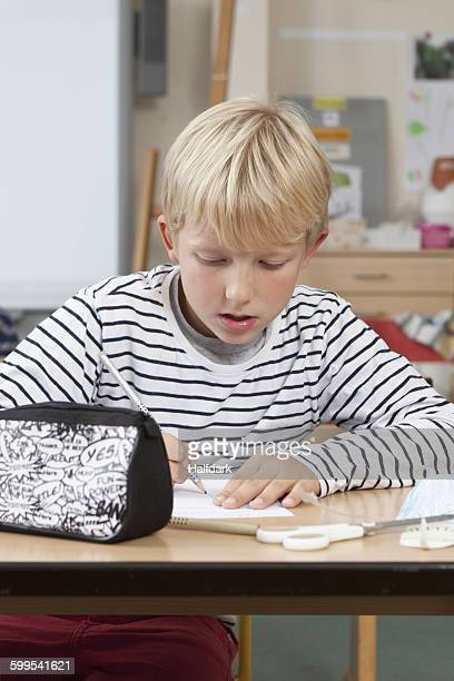 Boy drawing on paper in classroom