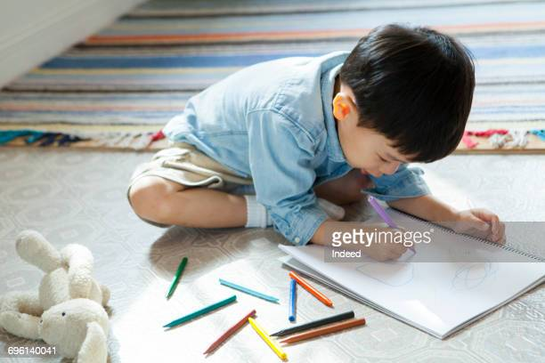 Boy drawing picture on note pad on floor